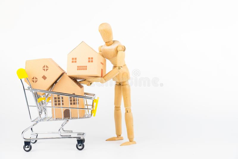 Wooden human mannequin holding shopping cart full of paper hose. Model, isolated on white background with copy space.Real estate concept, New house concept stock image