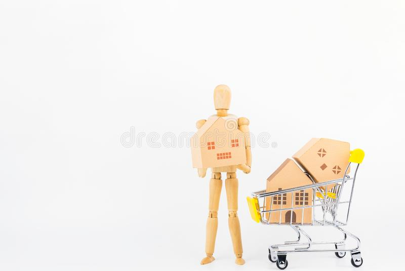 Wooden human mannequin holding shopping cart full of paper hose. Model, isolated on white background with copy space.Real estate concept, New house concept stock photo