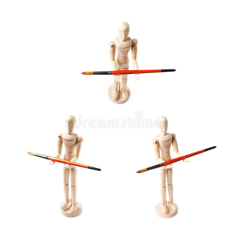 Wooden human statuette isolated. Wooden human statuette holding a drawing brush, composition isolated over the white background, set of three different royalty free stock photos