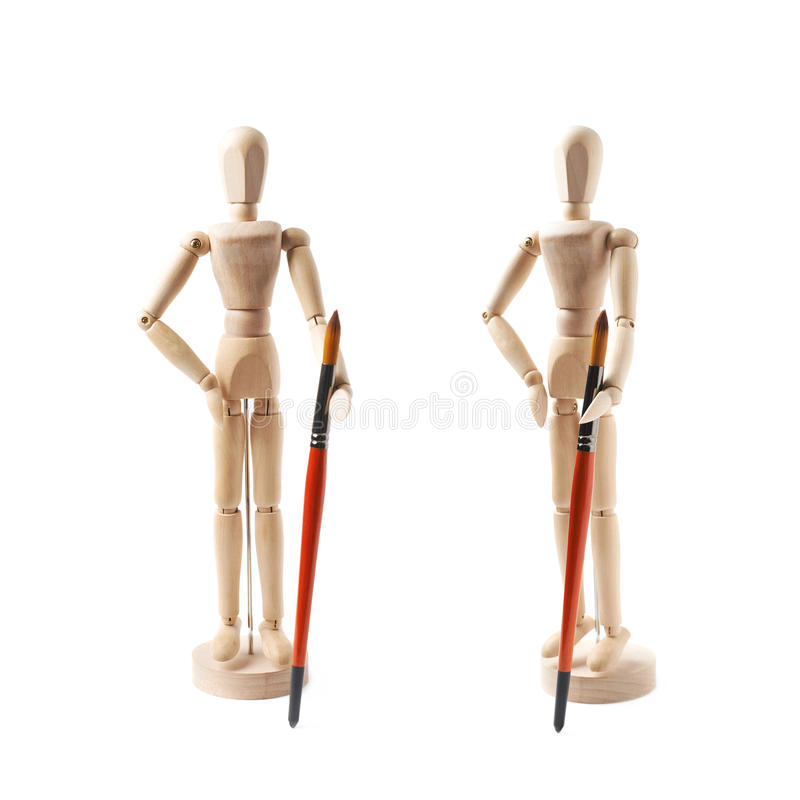 Wooden human statuette isolated. Wooden human statuette holding a drawing brush, composition isolated over the white background, set of two different stock image