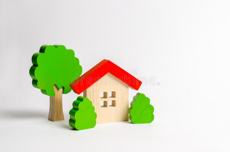 Wooden hut and tree figurines with bushes. The concept of a love nest. Country estate. Acquisition of affordable housing in a stock images
