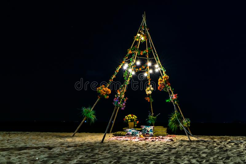 Wooden hutwith with light bulbs and flowers at night on the sand on the beach. Hutwith with light bulbs and flowers at night on sand on the beach, arch, archway stock photos