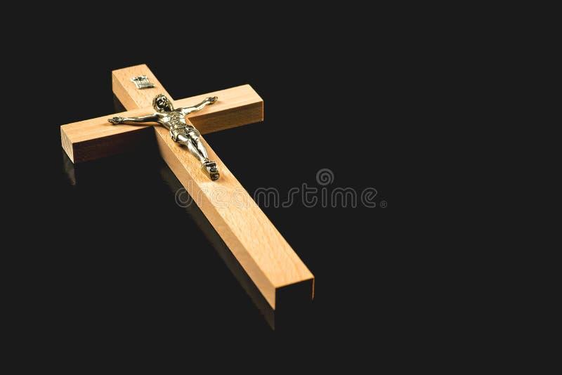 Wooden illuminated crucifix on a black background. A light brown wooden illuminated crucifix against a black background stock photos