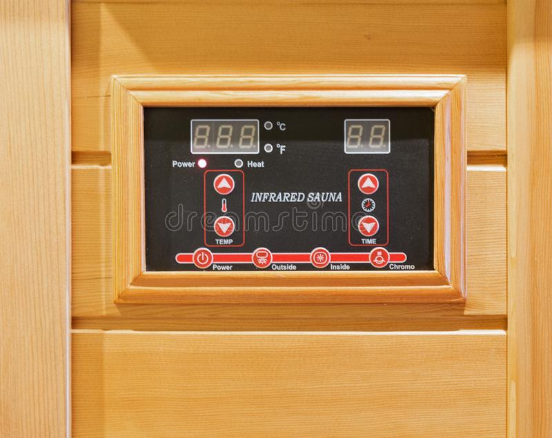 Wooden infrared sauna remote control royalty free stock photography