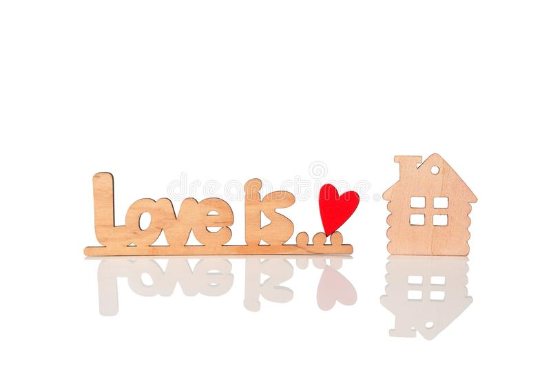 Wooden inscription love is, wooden red heart and a wooden house model. isolated on white background.  stock image