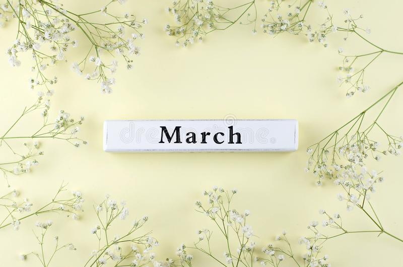 Wooden inscription of the spring month March on a yellow background royalty free stock photo