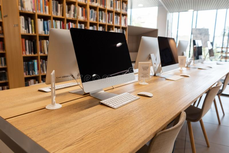 Wooden interior of the library with panoramic windows with a wooden table with computer monitors on it. Computer room royalty free stock photos
