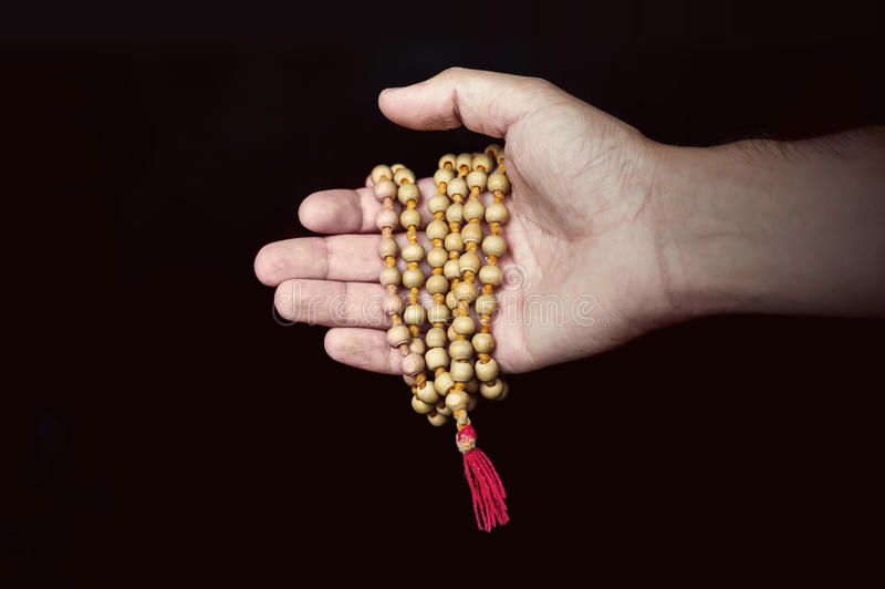 Wooden Islamic prayer beads in hand royalty free stock photo