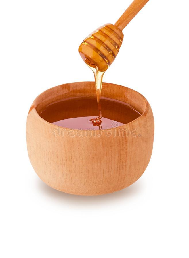 Wooden jar and honey bee dripping from dipper isolated on white background with clipping path. Side view stock photo
