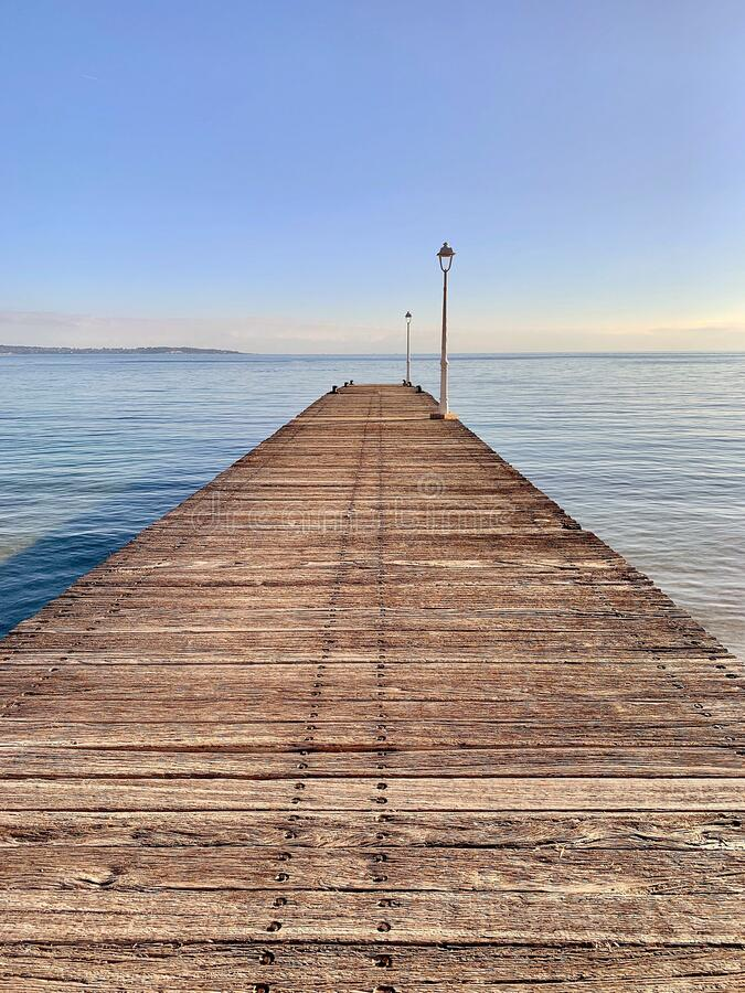 A wooden Jetty Boardwalk leading out to Sea royalty free stock photography