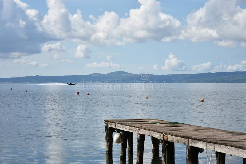 Wooden jetty for boats against a blue sky with some clouds. Floating buoys. Hills on background. Bolsena lake, Italy royalty free stock images