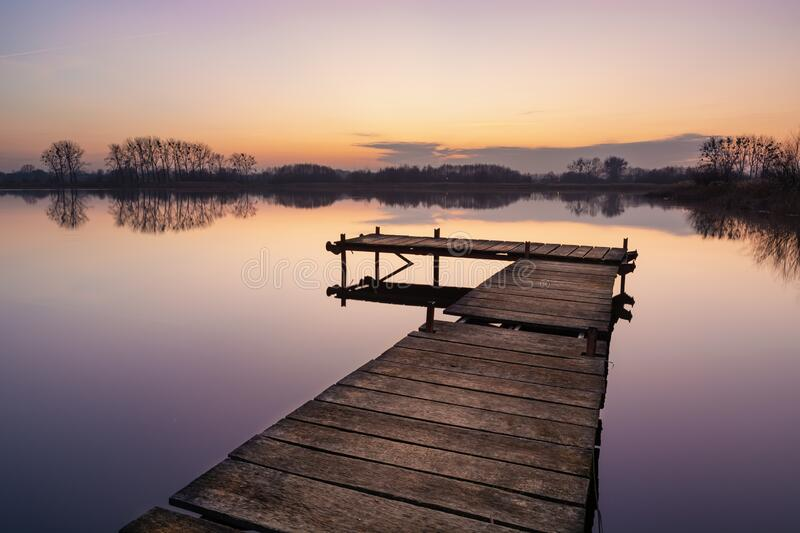 Wooden jetty and calm water surface on the lake, trees on the horizon. View after sunset stock photos