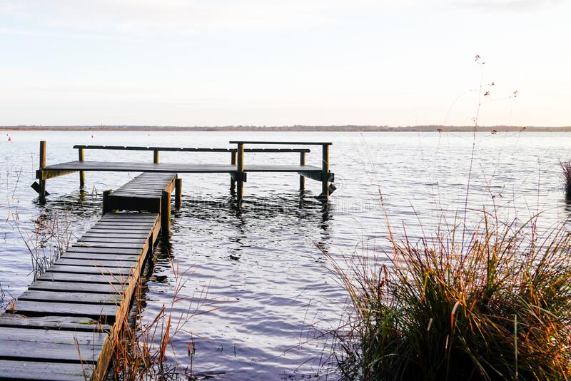 Wooden jetty fishing boat on lake of sanguinet biscarosse in landes france royalty free stock photography