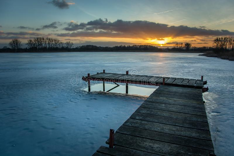 Jetty on a frozen lake, clouds and sunset royalty free stock photo