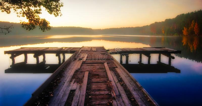 Wooden jetty in lake at sunrise. Wooden jetty in lake. Sunrise near lake, vibrant color sky before dawn royalty free stock photography