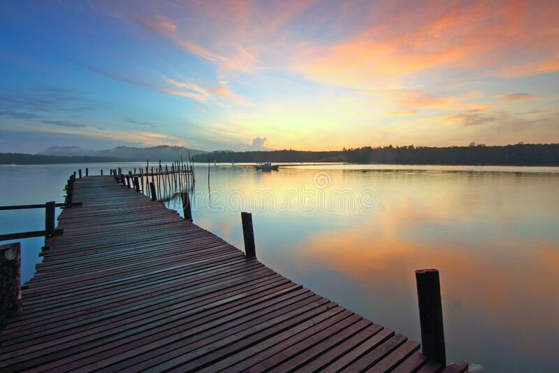 Wooden jetty on lake at sunset royalty free stock images