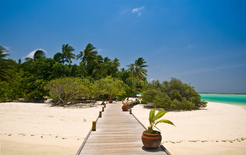 Wooden jetty leading to a tropical island royalty free stock photo
