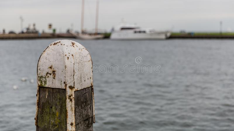 Wooden jetty pole with metal on a pier on a lake with calm waters and a boat in the background royalty free stock photo