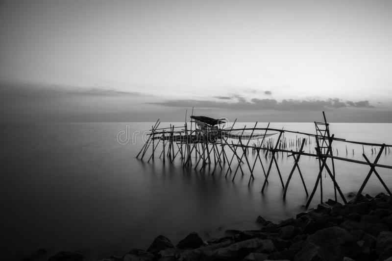 wooden Jetty with the rocky seaside during blue hour. Long Exposure Black and White royalty free stock images