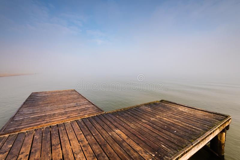 Wooden jetty by the sea. During the morning fog. Baltic Sea, Sopot Poland stock photography