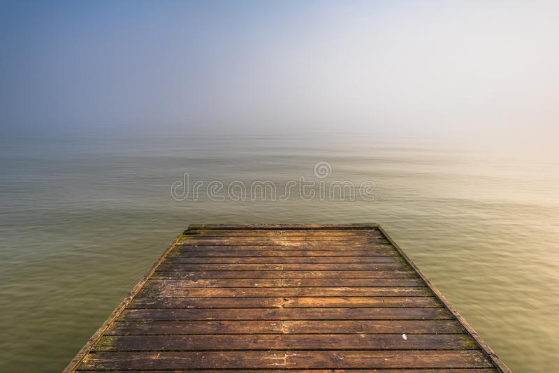 Wooden jetty by the sea. During the morning fog. Baltic Sea, Sopot Poland royalty free stock photos