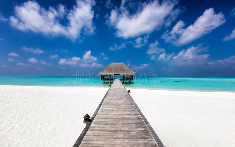 Wooden jetty to a water lodge on a tropical beach royalty free stock images