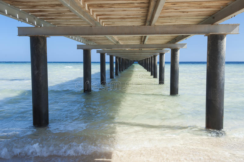 Wooden jetty on tropical beach royalty free stock images