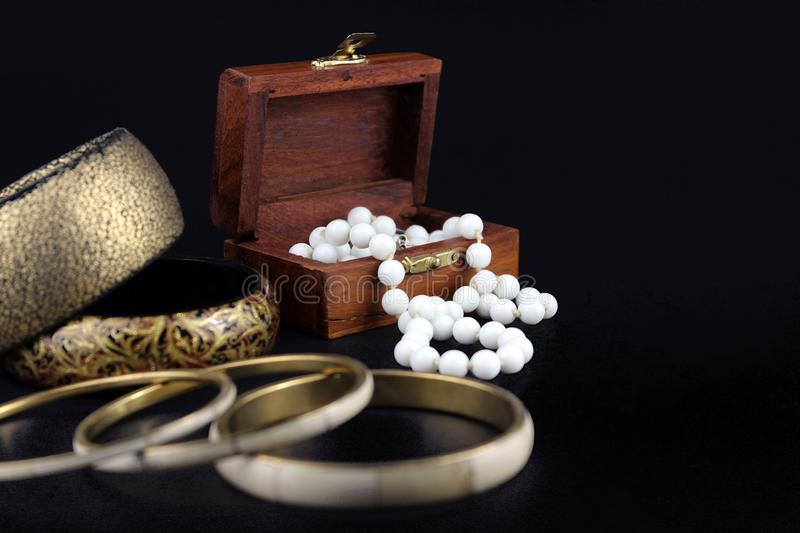 Wooden jewelry box. A small wooden jewelry box with pearls and bracelet on black background royalty free stock photography