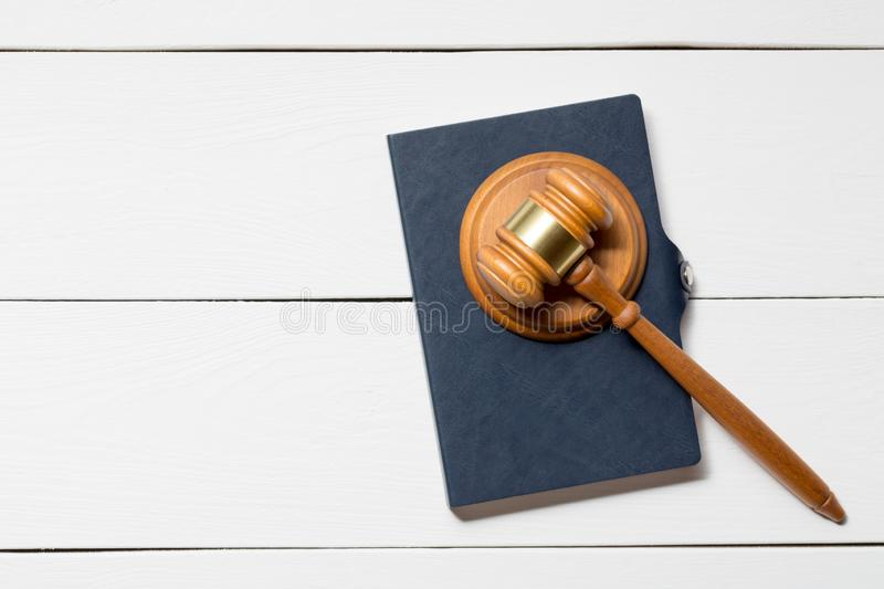 Wooden judge gavel hammer with a book on white wooden table background. Copy space royalty free stock images