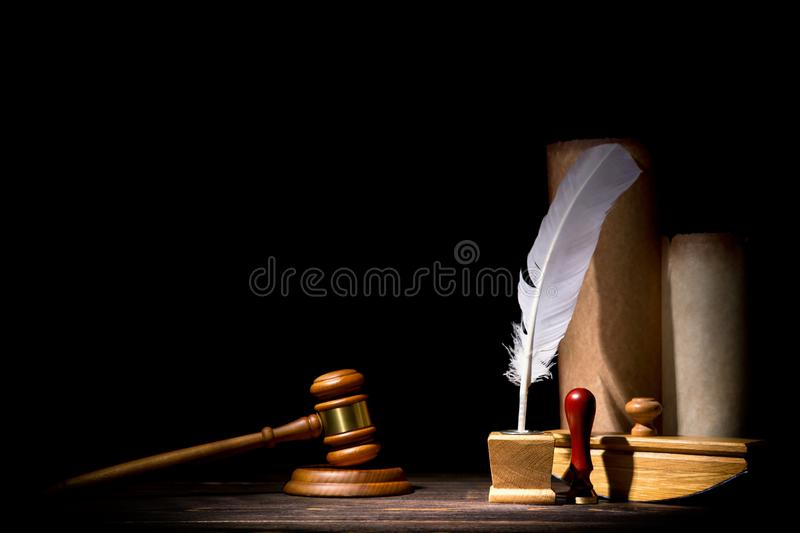 Wooden judge gavel hammer, old inkstand with feather quill, blotter, seal near scrolls against black background. Dramatic light. royalty free stock photo