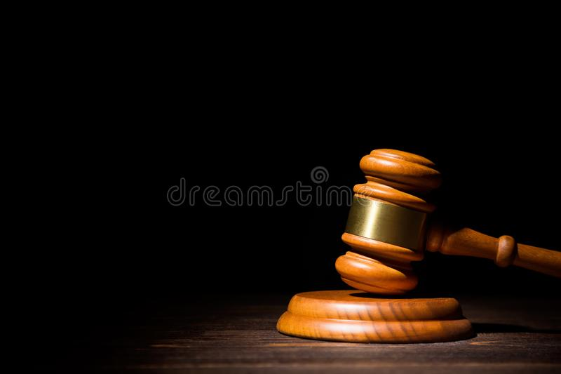Wooden judge gavel hammer on wooden table against black background. Dramatic light. Copy space royalty free stock photo