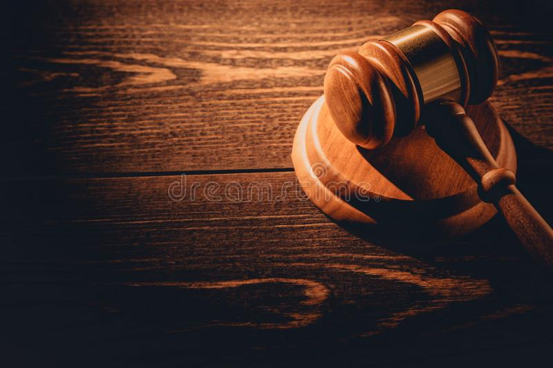 Wooden judge gavel hammer on wooden table background. Dramatic light. Copy space royalty free stock images