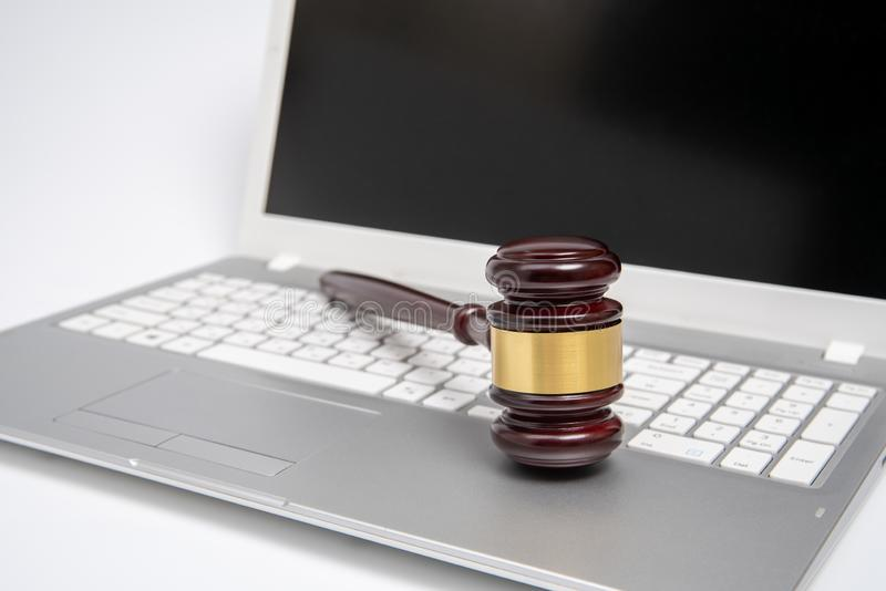 Wooden judge gavel on a silver laptop computer, cyber law or online auction concept. stock photography