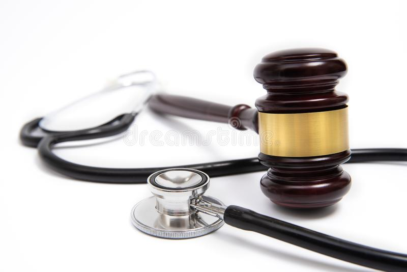 A wooden judge gavel and stethoscope isolated on white background. Medical dispute concept. royalty free stock images