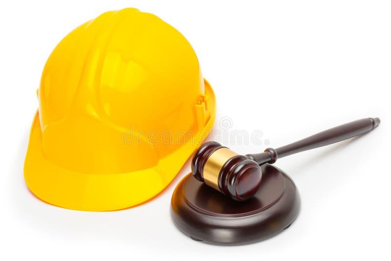 Wooden judge gavel with yellow protective helmet - studio shoot stock image
