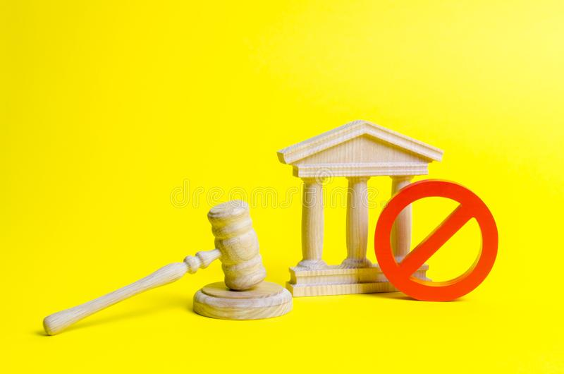 Wooden judge hammer and government building on a yellow background. Court. Concept of the state judicial system. Laws and the constitution, lack of Supremacy stock photo