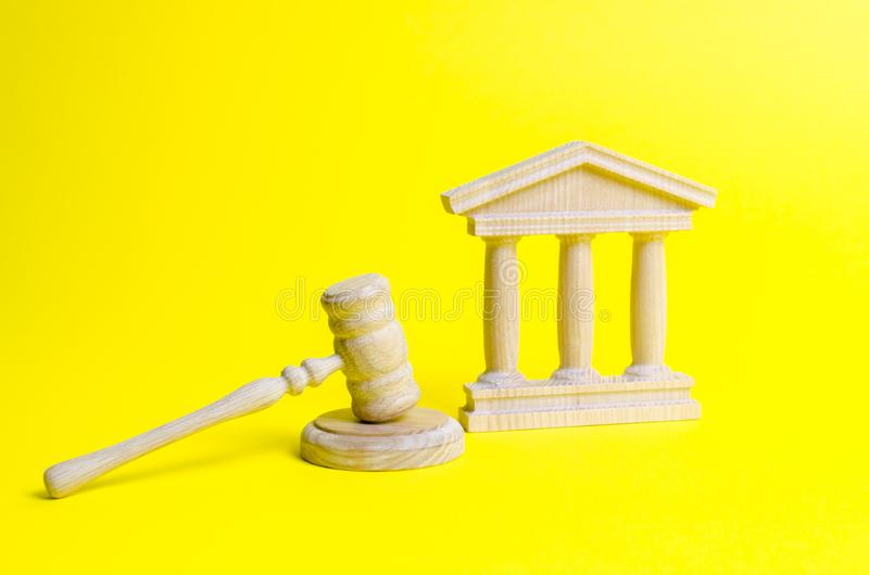 Wooden judge hammer and government building on a yellow background. Court. Concept of the state judicial system. Prohibitions. And criminalization, repression stock photos