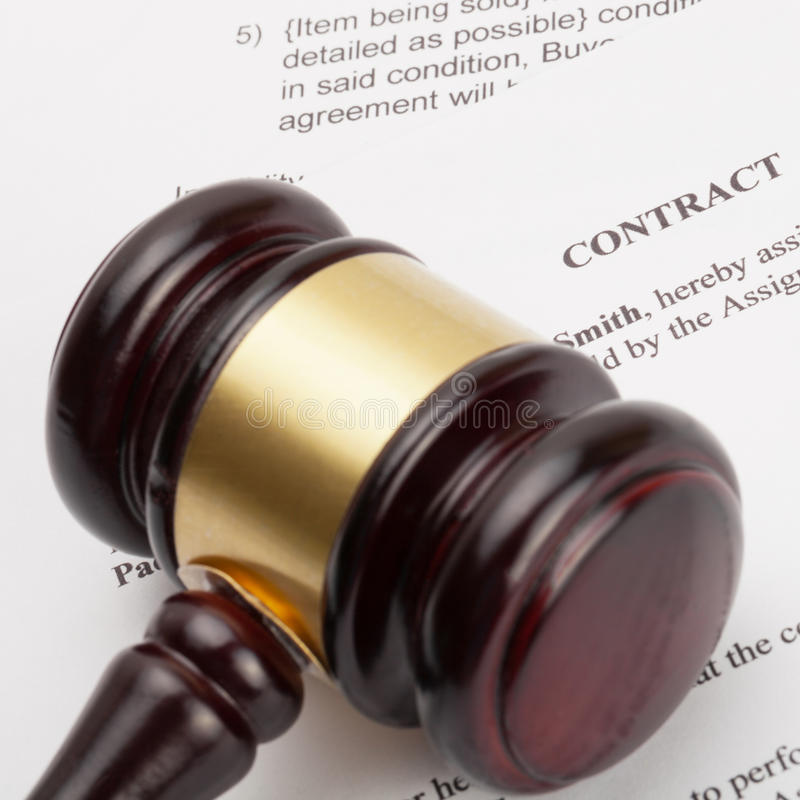 Wooden judge's gavel and contract - close up shot. Judge's gavel and contract - close up shot stock photography