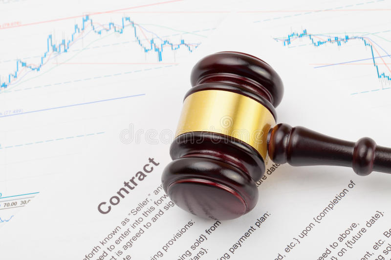 Wooden judge`s gavel over some financial document - close up studio shot stock photos