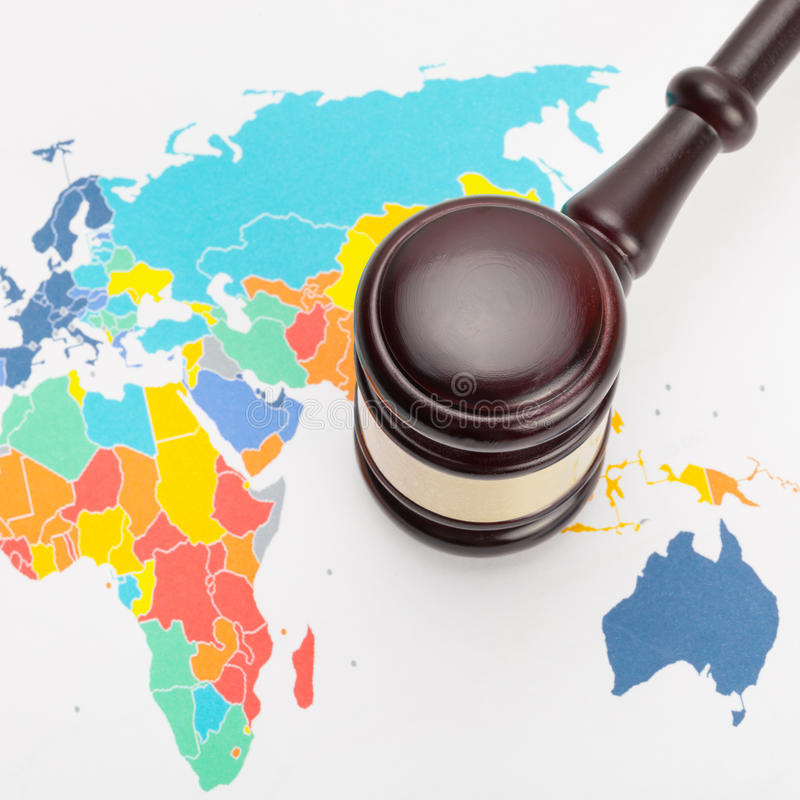 Wooden judge's gavel and over world map - close up shot. Judge's gavel and over world map - close up shot royalty free stock photography