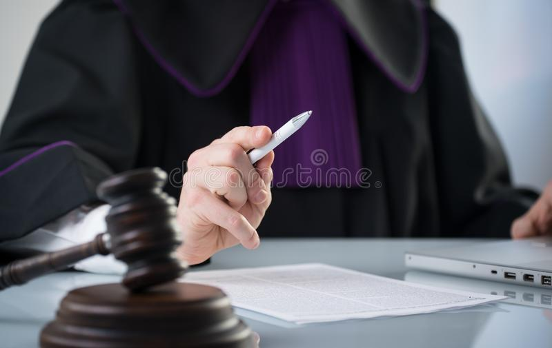 Wooden judge`s gavel on a white countertop. Judge on a white background. Judgment of the Court. Law Concept. Wooden judge`s gavel on a white countertop. Judge royalty free stock photography