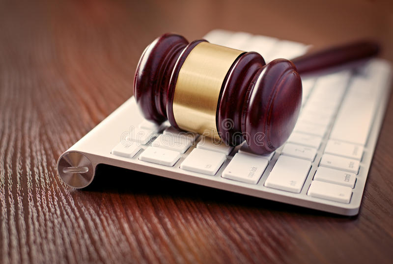 Wooden judges gavel on a computer keyboard. Receding view with focus to the head with its brass decoration conceptual of online law enforcement and auctions royalty free stock photo
