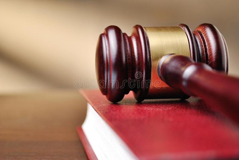 Wooden judges gavel on a law book stock images