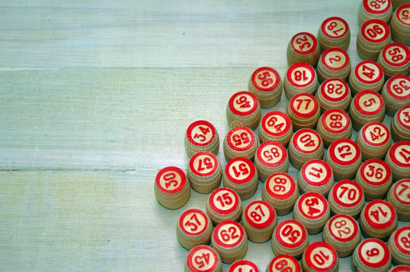 Wooden kegs, cards and chips for a game in a lotto. Bingo or lotto game. Wooden kegs of lotto on cards. Cards and chips for playing bingo on a white table stock photo
