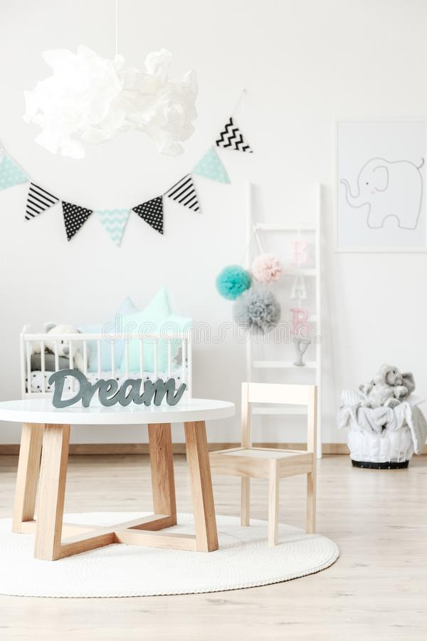 Wooden kid`s table and chair. On white round carpet in bright room with ladder and pompons royalty free stock photos