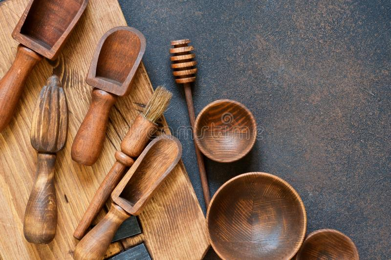 Wooden kitchen accessories: plate, rolling pin, board, spatula. On a concrete background. Top view. Kitchenware stock photo