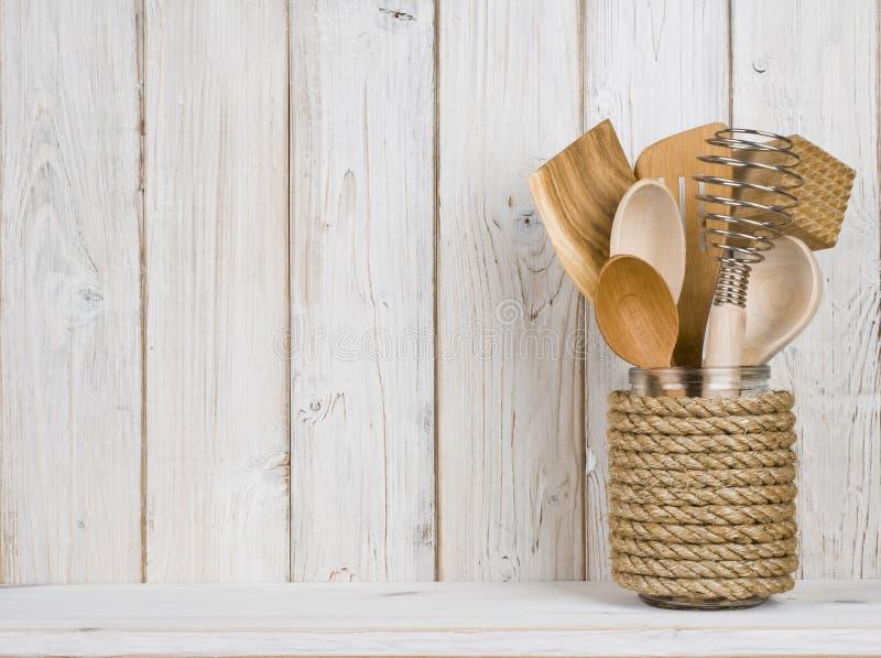 Wooden kitchen cooking utensils in handmade storage pot on shelf.  stock image