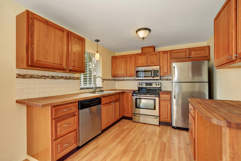 Wooden kitchen interior with stainless steel appliances. And mosaic back splash trim. Northwest, USA royalty free stock images