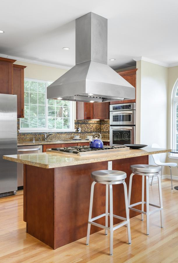 Kitchen island in luxury home with stainless steel appliances. Wooden Kitchen in luxury home with, kitchen island, stainless steel appliances, granite work royalty free stock photo
