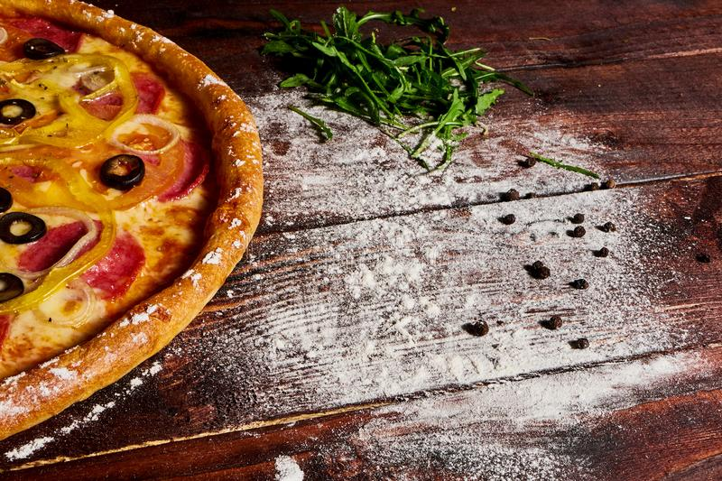 Wooden kitchen table with pizza sprinkled with flour royalty free stock image